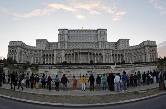 Protestors link hands as they form a human chain around Parliament palace in Bucharest during a demonstration against plans to open Europe's biggest open-cast gold mine in Romaina